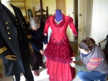 Stella a Volunteer working with a textile conservator to put costume on display