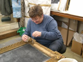 Sheila consolidating gilding on a frame